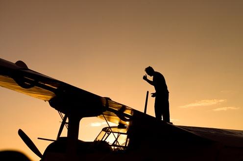 Sombra de persona sobre avión con fondo dorado-1383